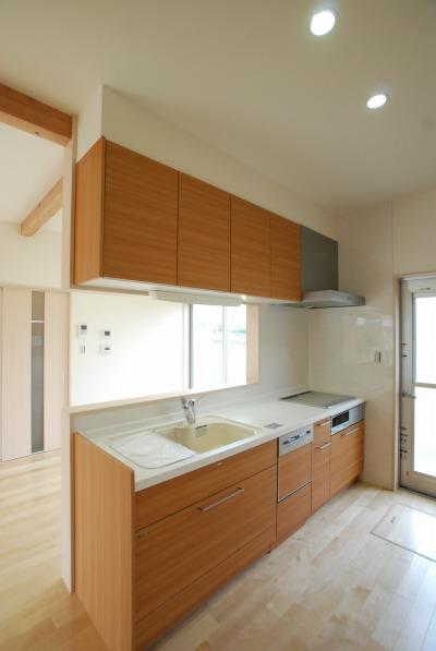 木目調をセレクトしたキッチンはナチュラルテイスト。カップボードとパントリーを取り付け、収納量を確保しました。また上下分離タイプのカップボードの間に窓を設け開放感を出しています。